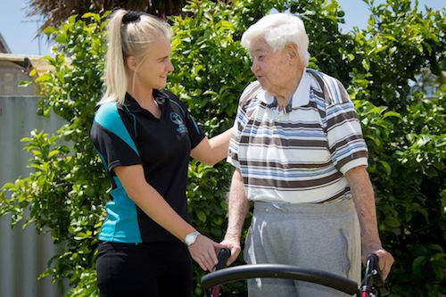 Physiotherapist helping senior in the garden